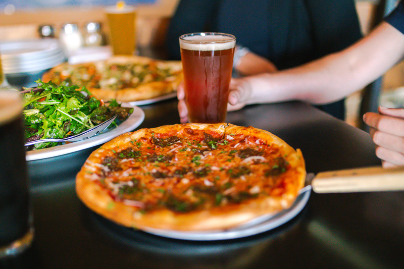 Pizza beer and salad on a table at Bridger Brewing in Bozeman