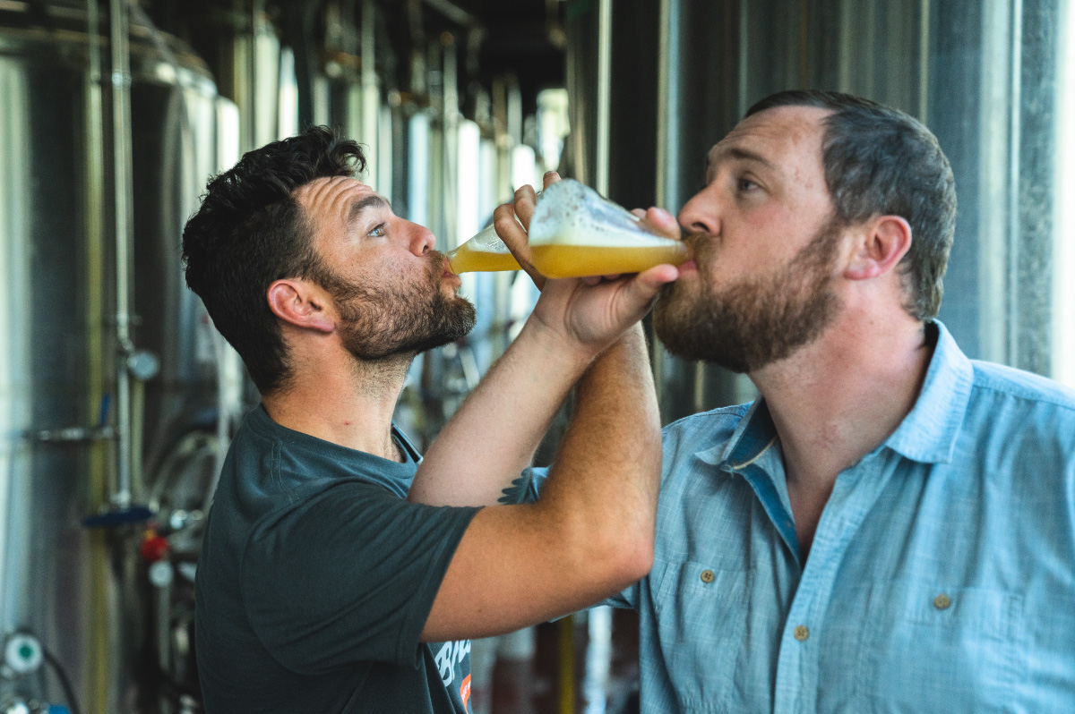 Brewers testing beer by linking arms and drinking out of beakers