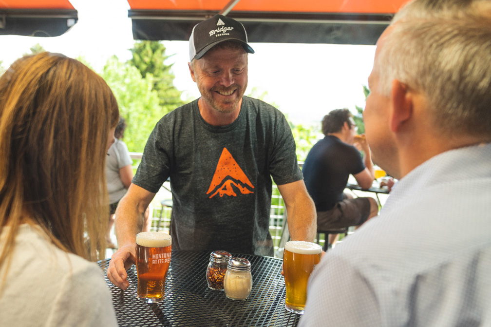 Bridger owner serving beer to guests outside at Bridger Brewing in Bozeman