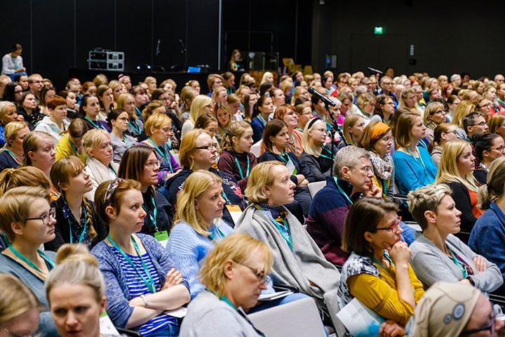 Suuri joukko osallistujia kuuntelemassa luentoa suuressa salissa