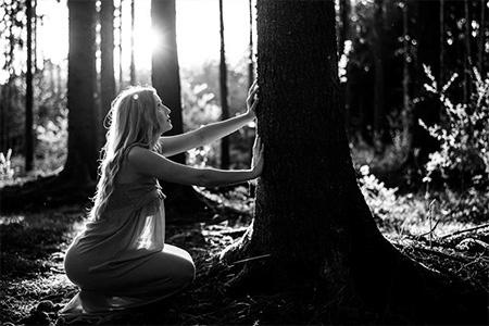 A woman touching a tree