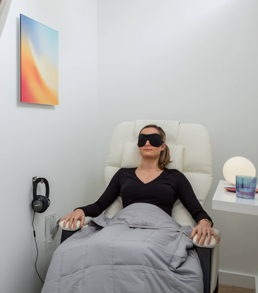 A woman with an eye mask on, covered in a blanket, in a clinical setting receiving ketamine treatment