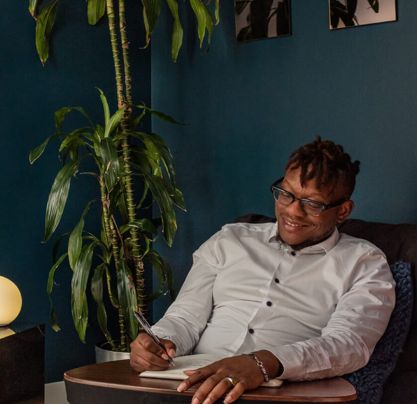 A smiling man doing integration journaling in a chair next to a plant