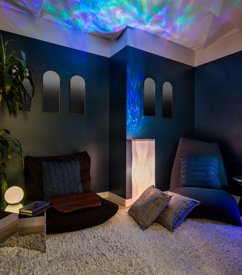 A comfortable, low-lit room with floor pillows and chairs, and a psychedelic pattern on the ceiling