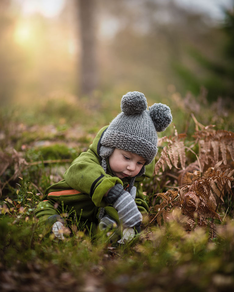 A toddler sitting on the forest grass