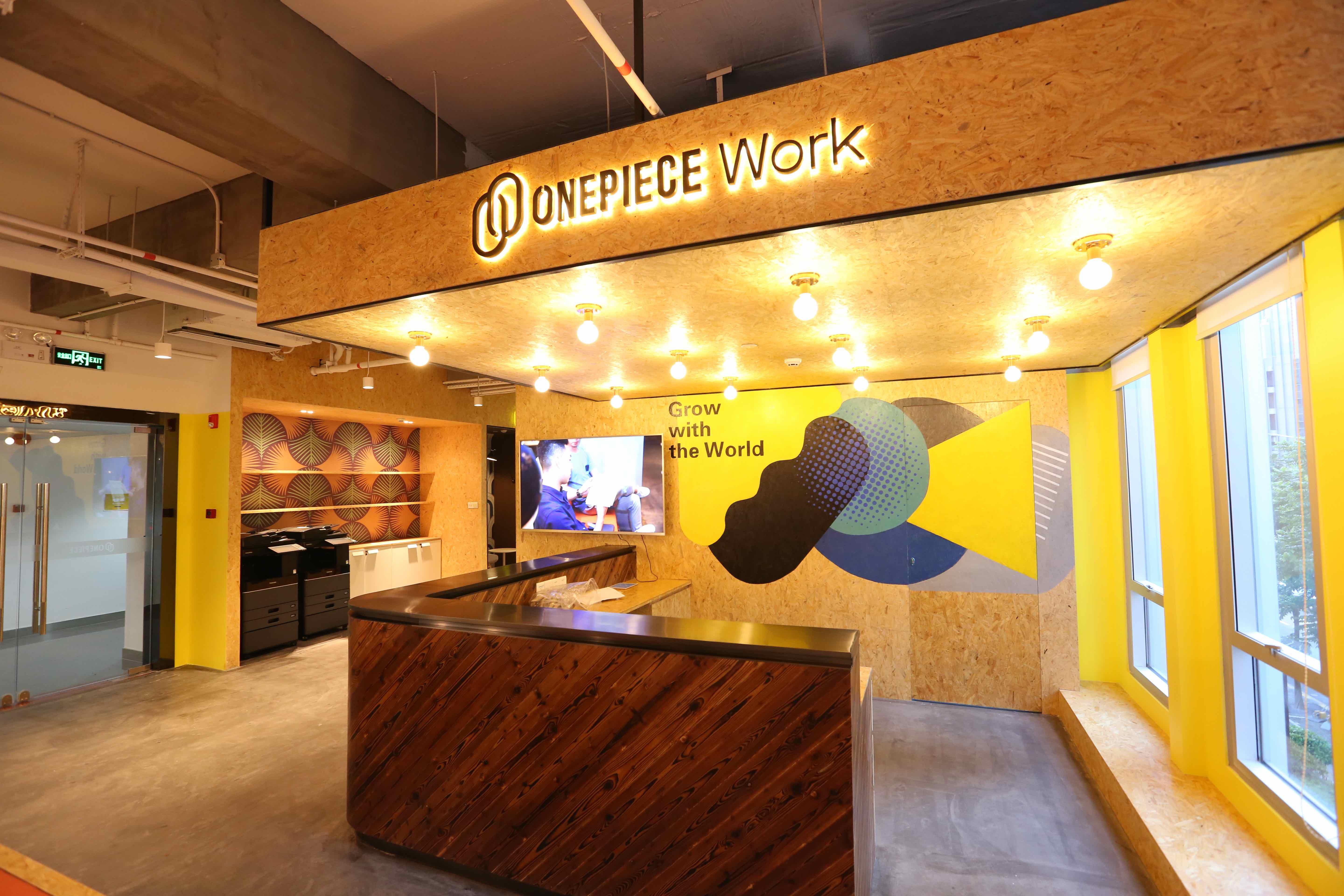 OnePiece Work Shenzhen location lobby featuring rustic wood finishes, custom light fixtures, and stylized signage