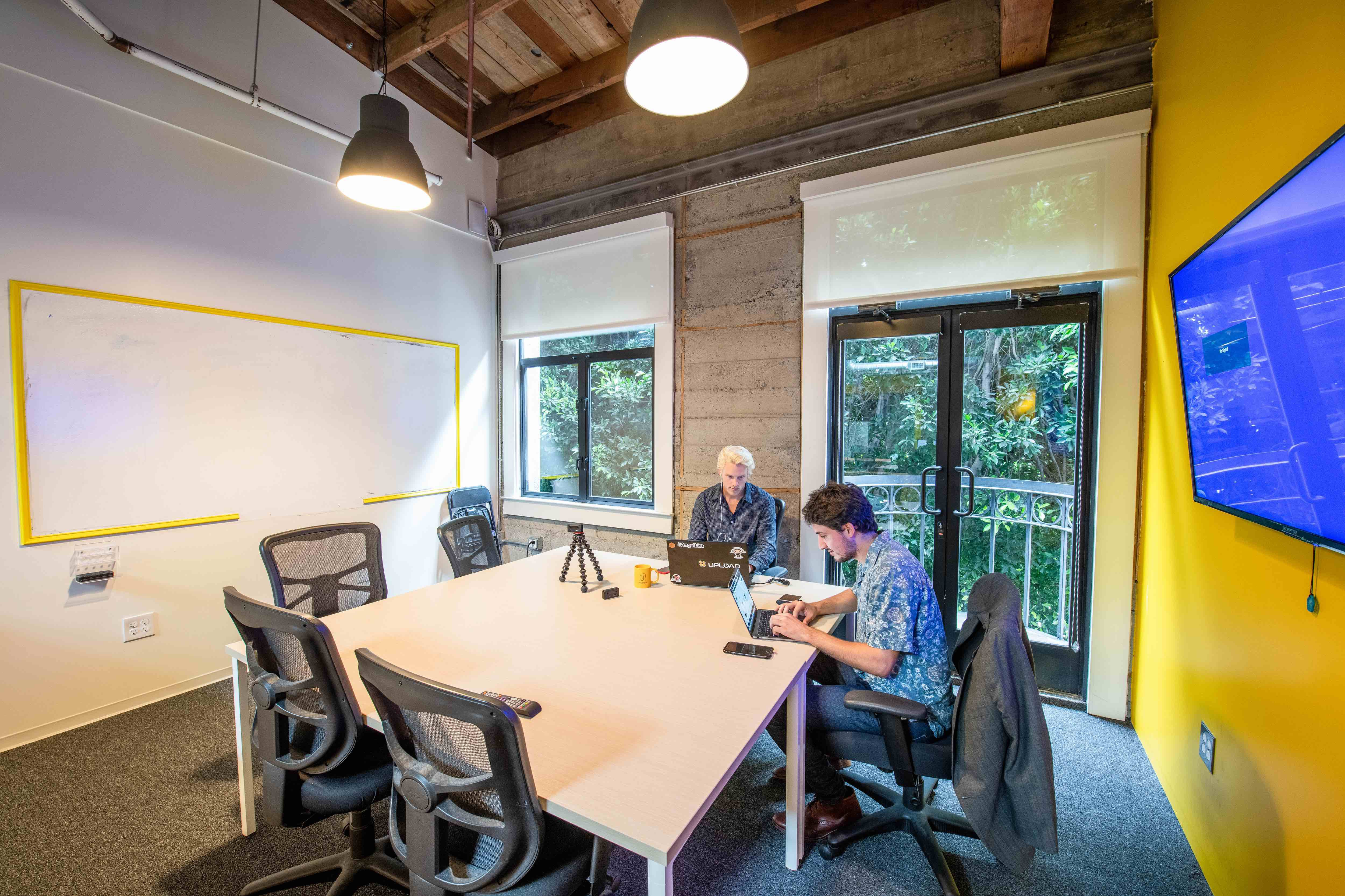 Two young professionals on laptops collaborate in OnePiece Work San Francisco coworking space