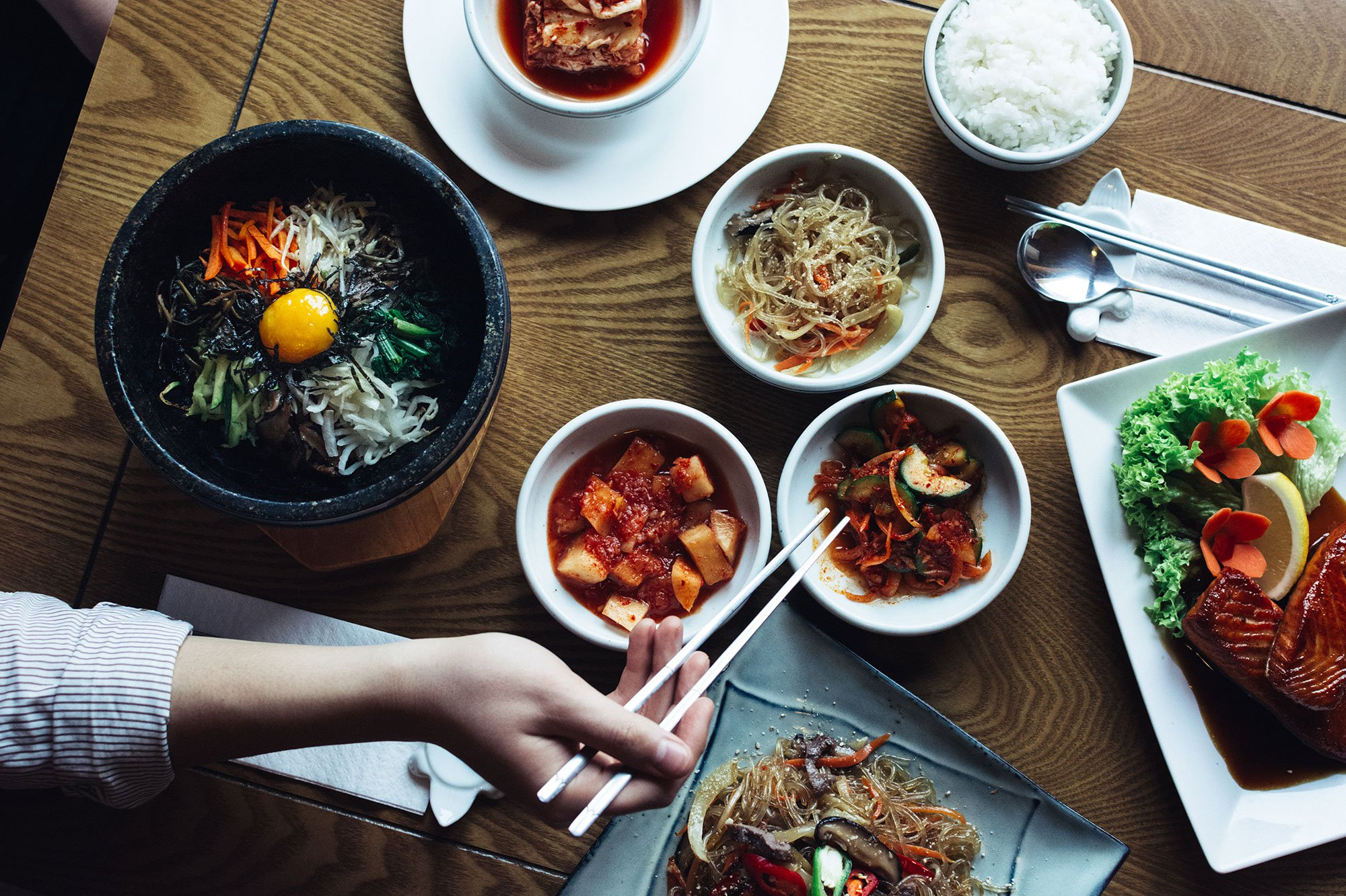 Overhead view of a wooden table set with various Korean dishes as woman's hand holding chopsticks enters the frame