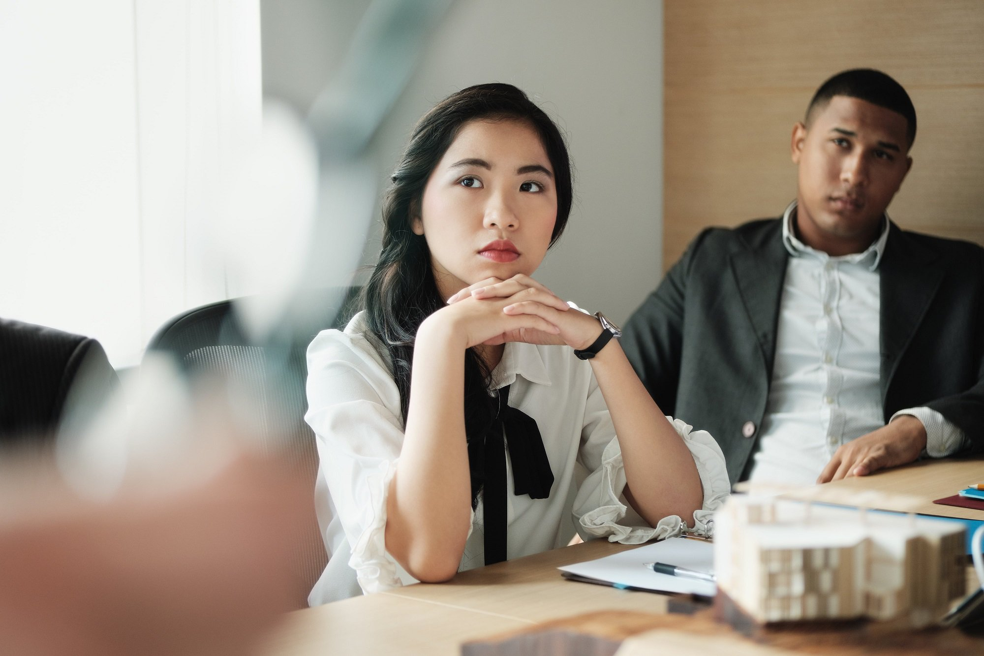 Young Asian woman listens intently in an office setting