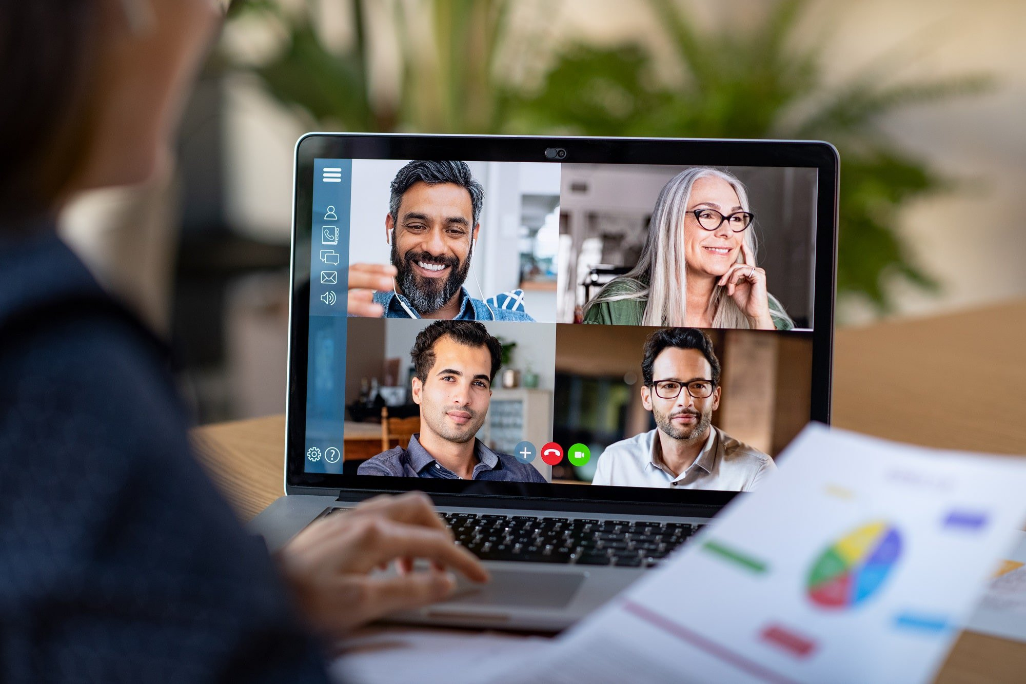Laptop screen displays a video conference between various multi-ethnic co-workers