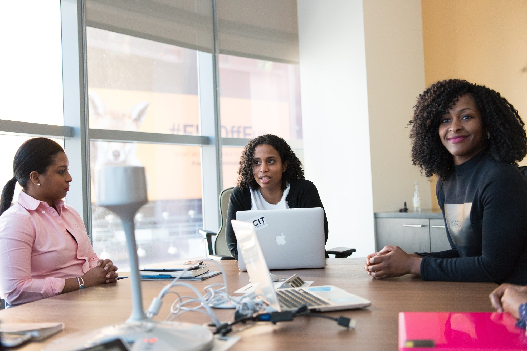 Three businesswomen sit at a conference table