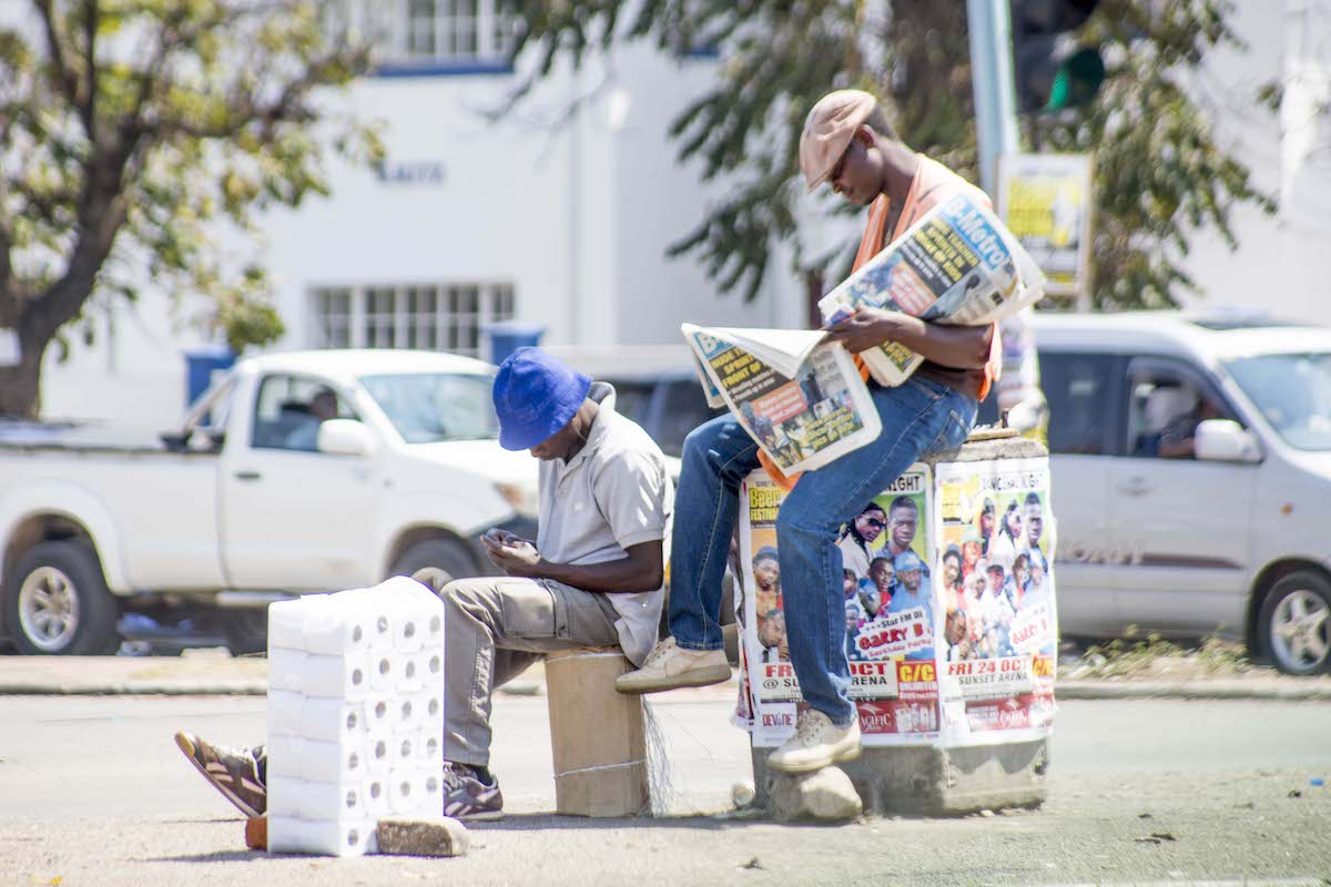 Men reading newspaper, photo by Steven Chikosi