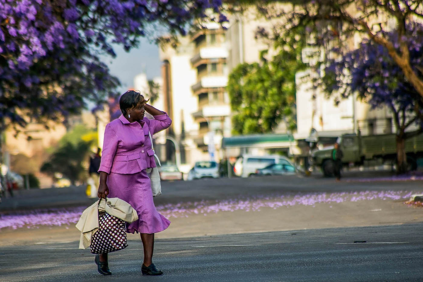 Woman crossing a street whilst Jacaranda blossom, photo by Steven Chikosi