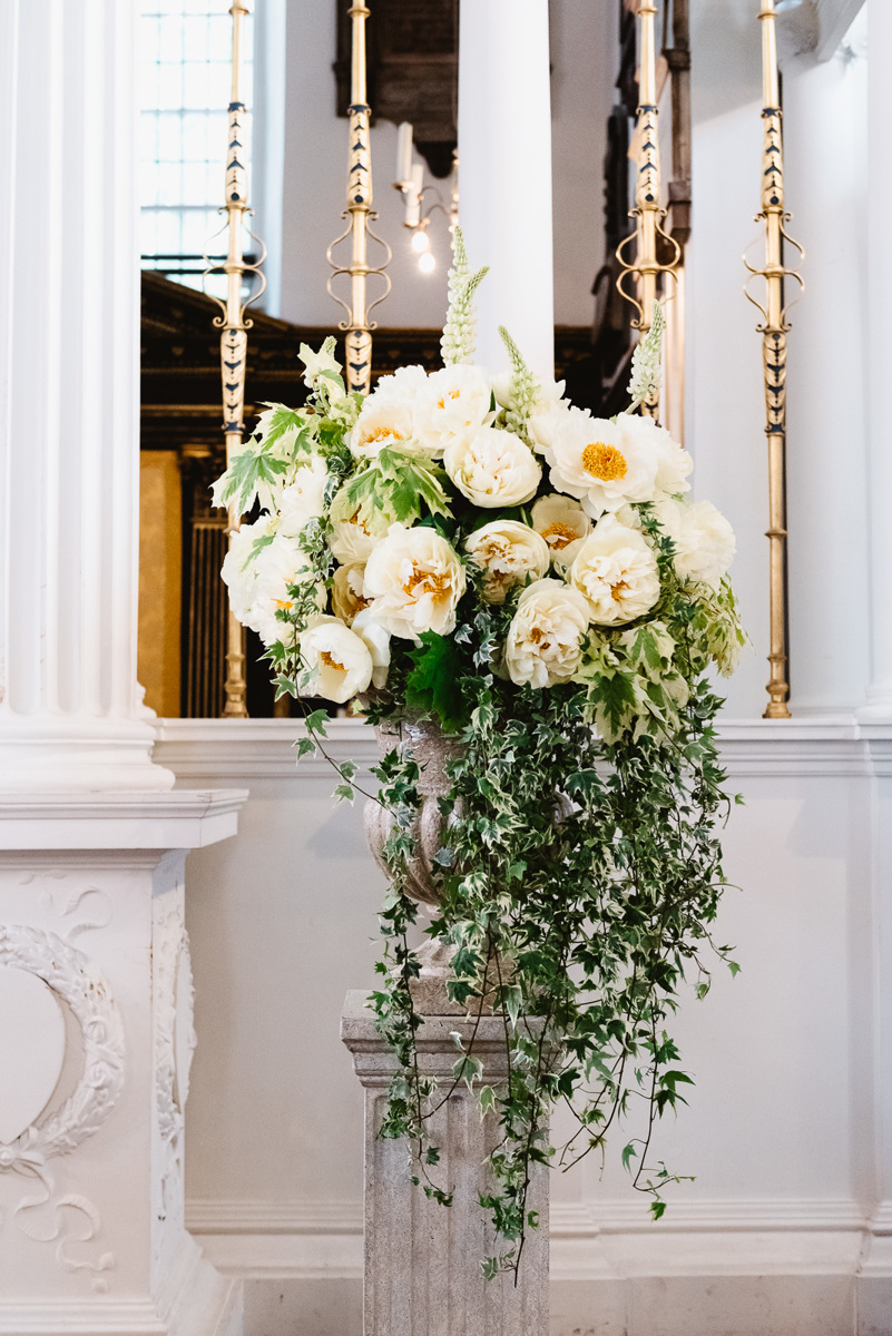 Large church flower arrangement in Mayfair, London with ivy and peonies