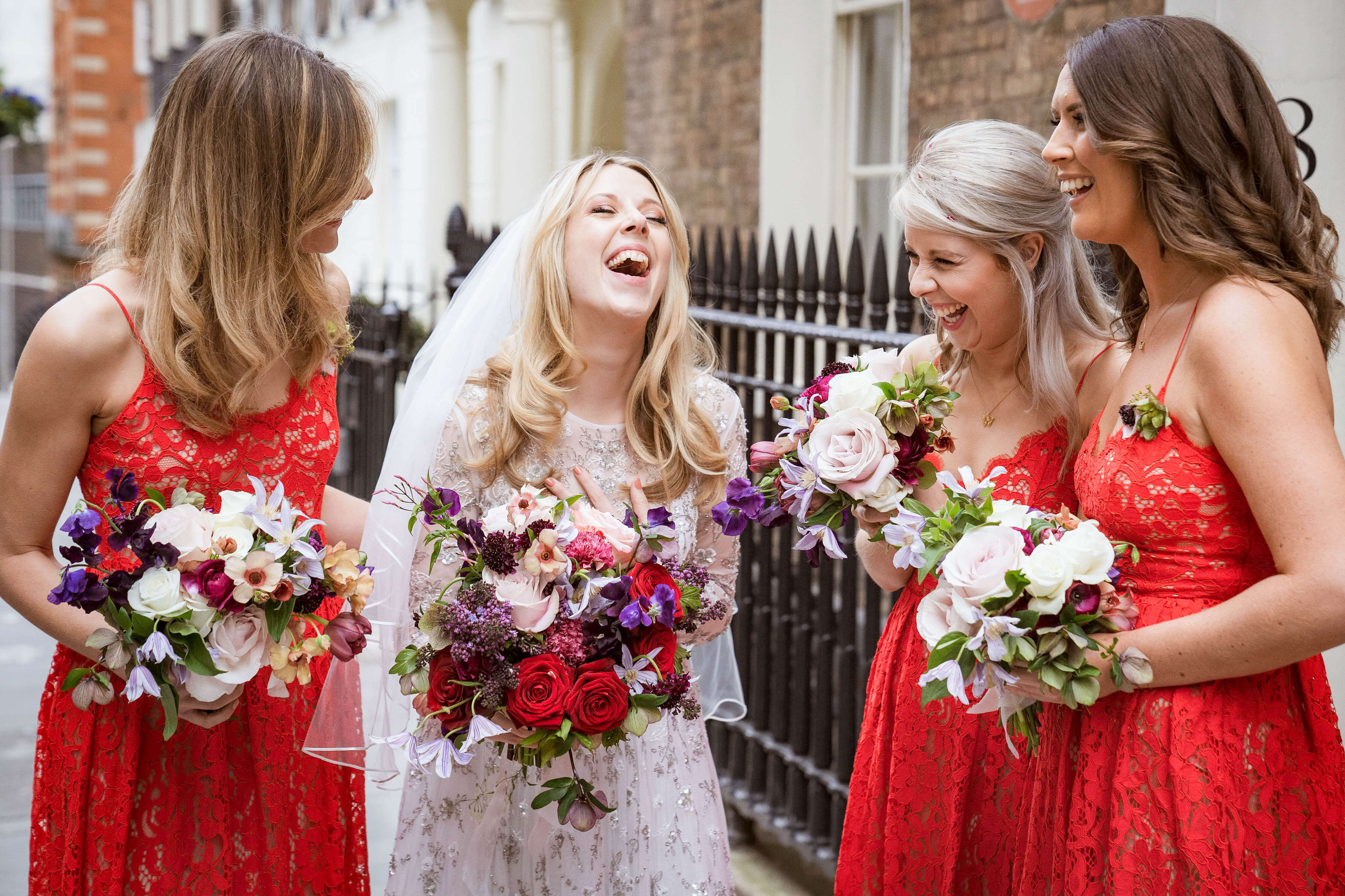 Bride with Wedding bouquet. Bridesmaids wearing Red Dresses