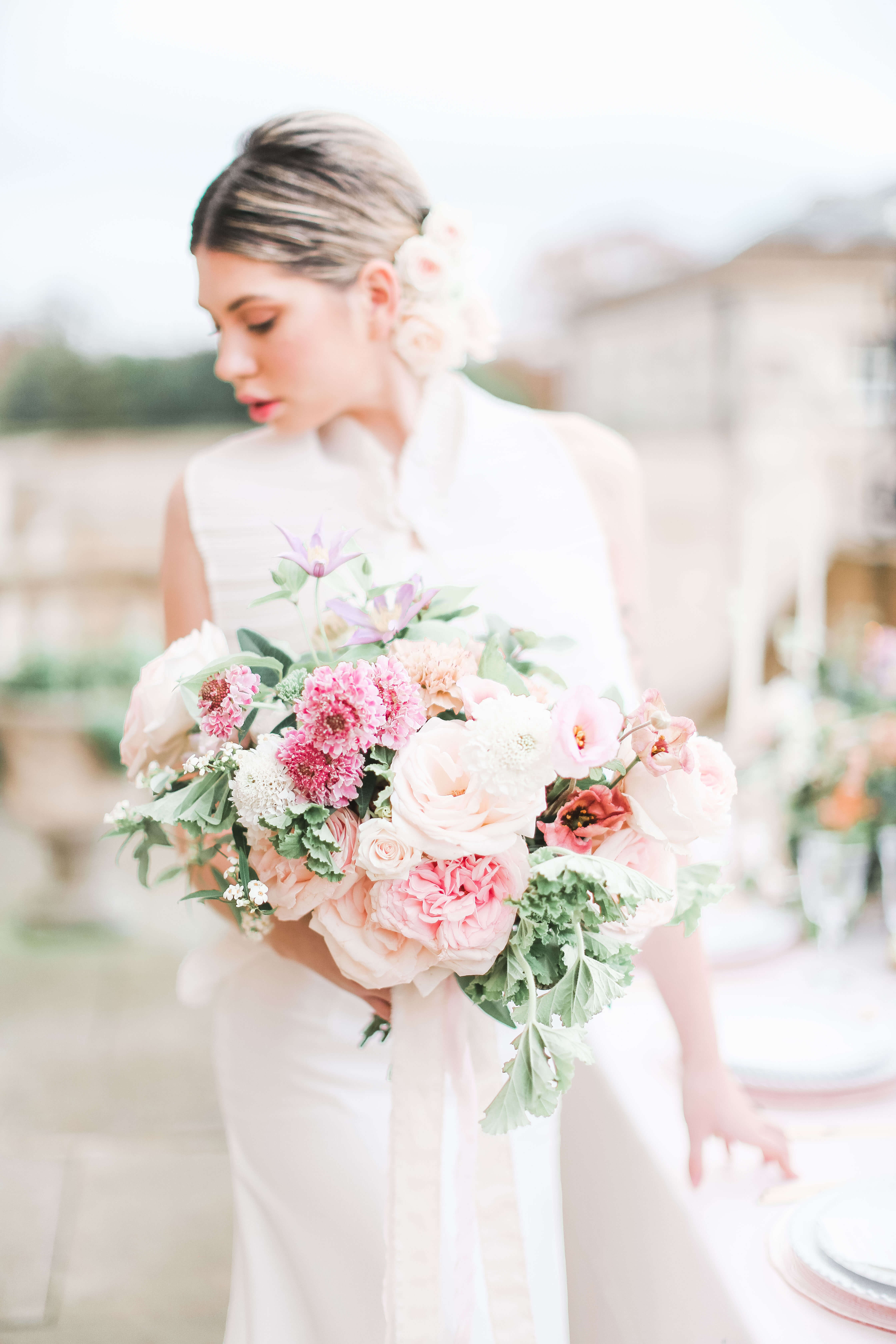 Bride with a pink wedding bouquet with Japanese roses, scabiosas, earthy eustomas, clematis and geraniums