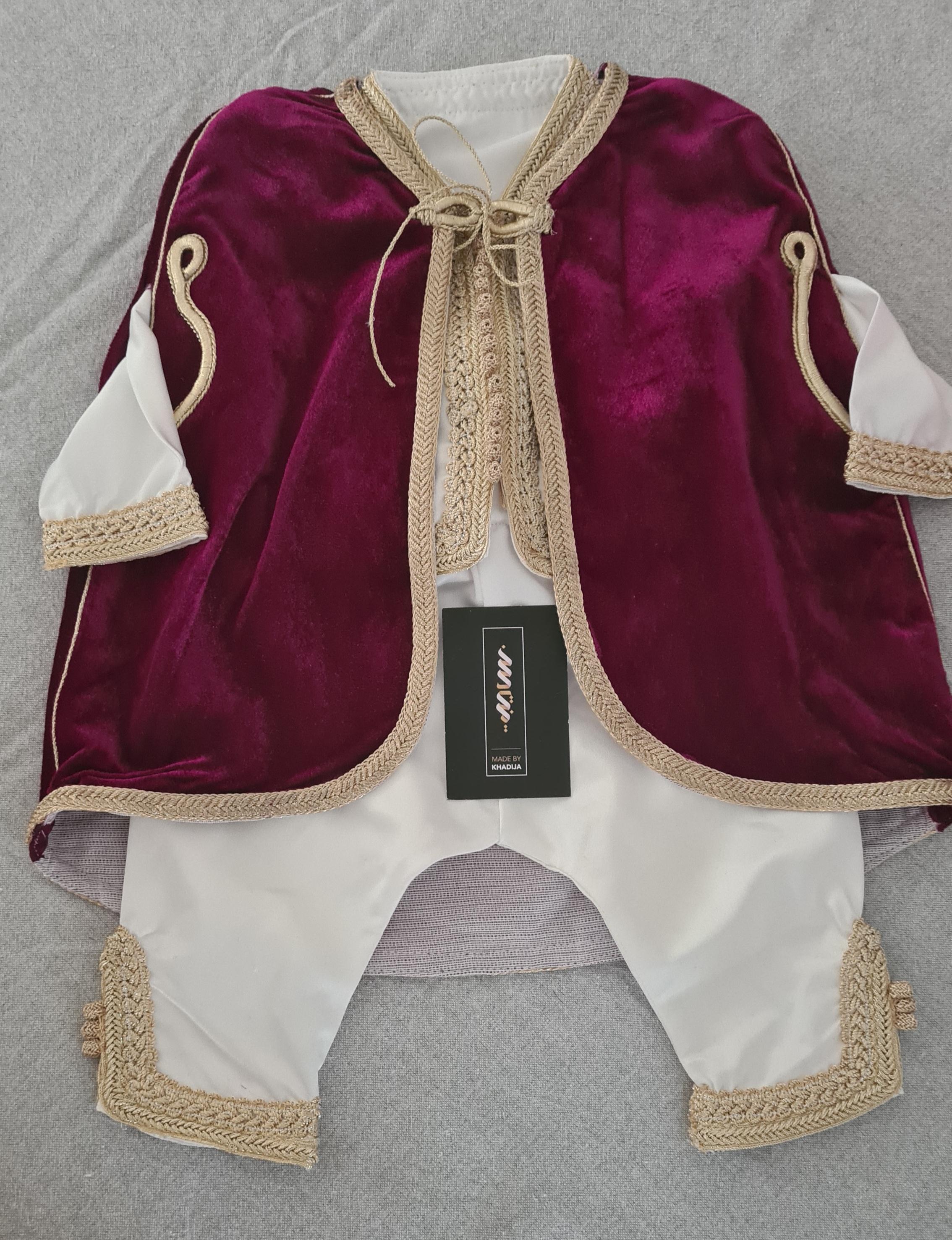 Witte baby jabador met bordeauxrood jasje