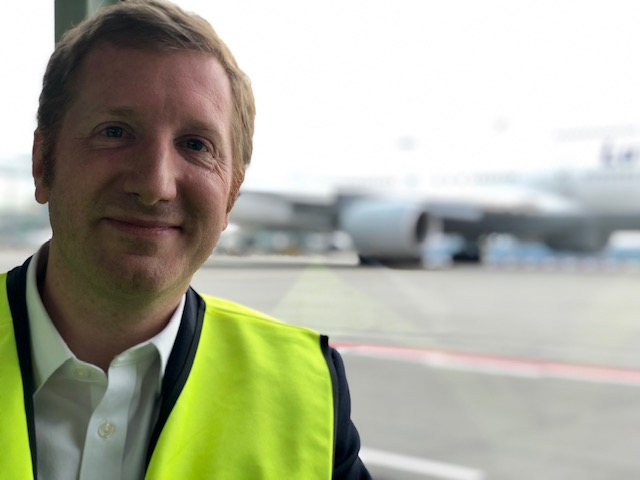 Jan Cristoph Oetjen wearing a fluorescent vest at an airport in front of a transport aircraft