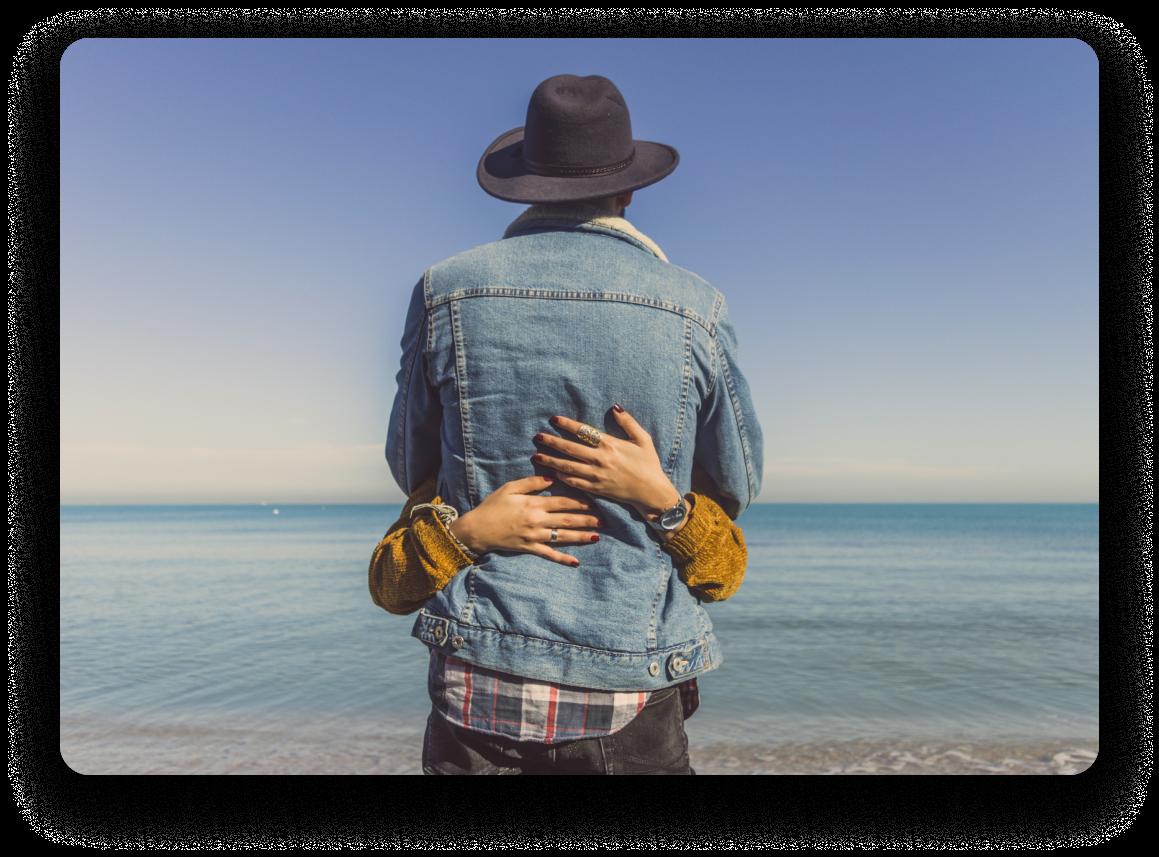 Woman hugging man wearing a fedora