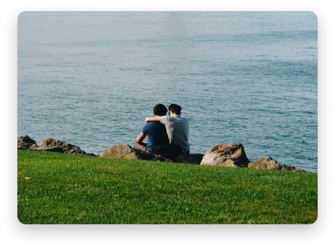 Couple looking down at body of water from a cliff