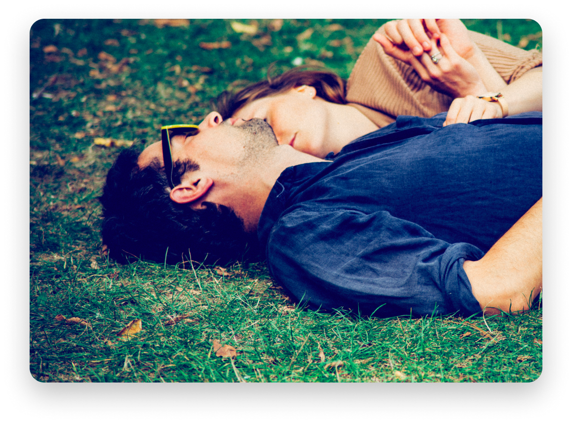 Man and woman laying down on grass