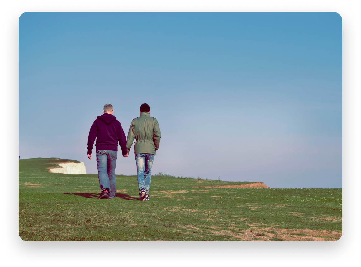Two men walking on grass while holding hands