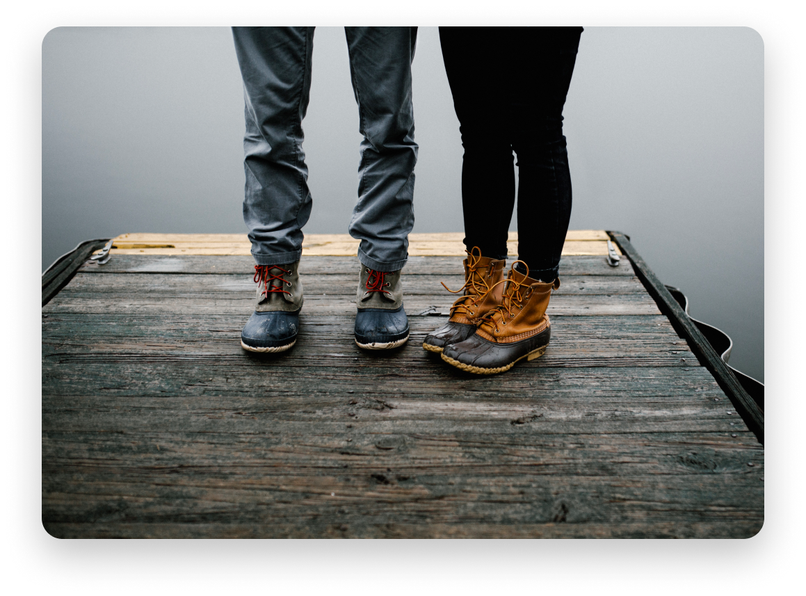 Man and woman on dock wearing boots
