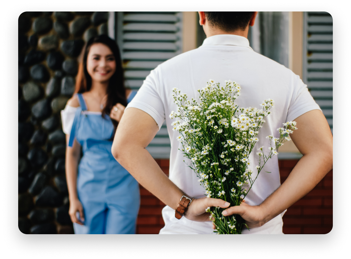 Man about to surprise a woman with a bouquet of flowers