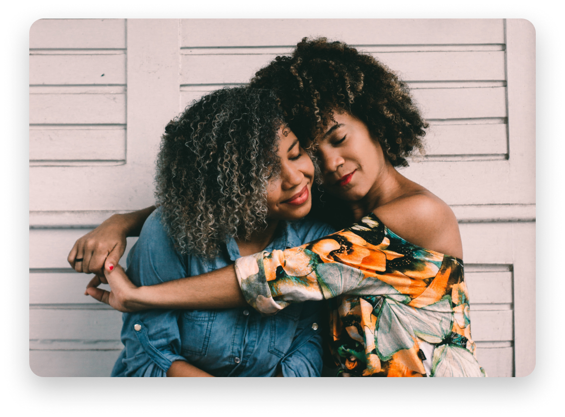 Dark-skinned women hugging with eyes closed