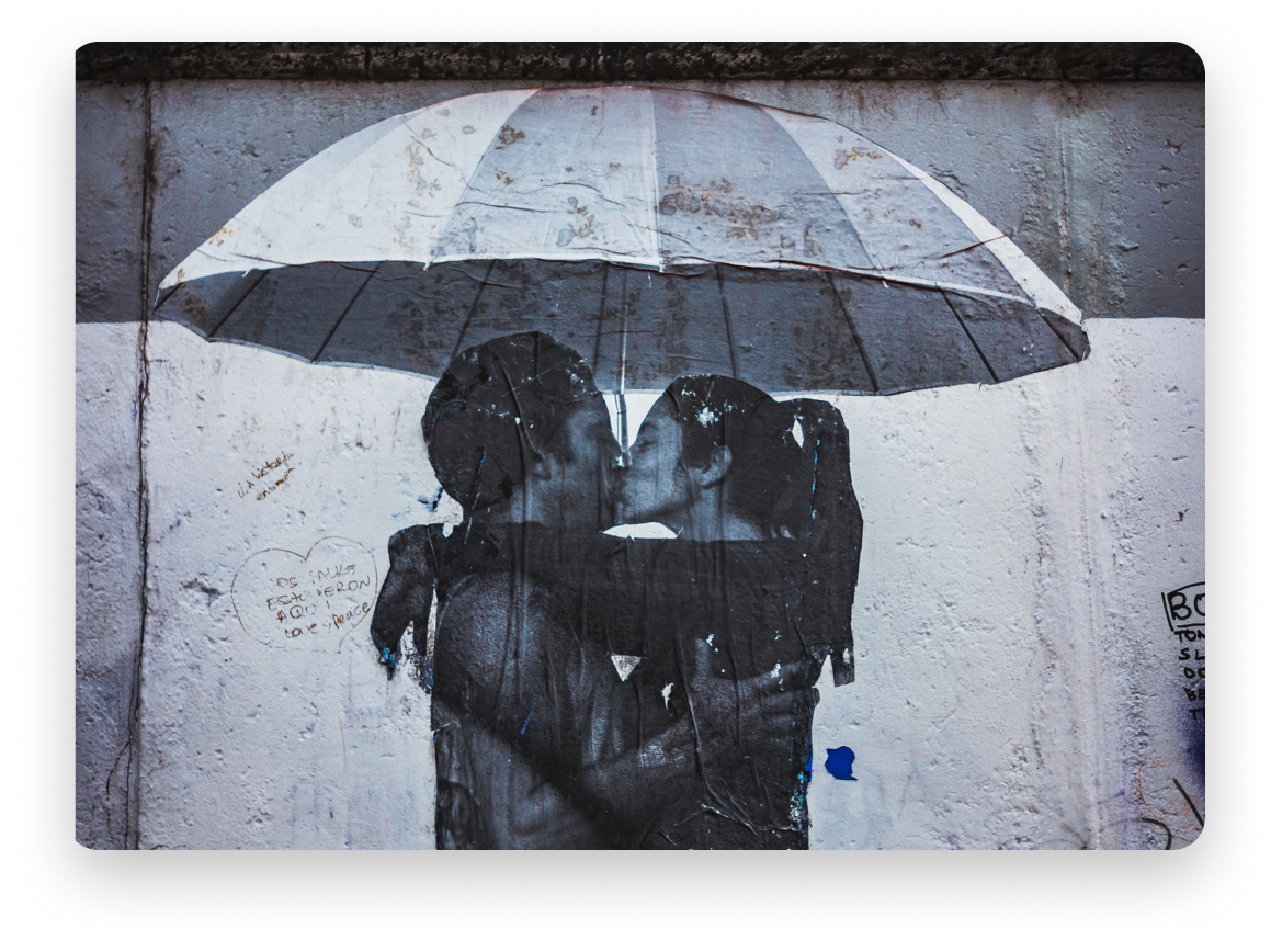 Illustration on a wall of a couple kissing under an umbrella