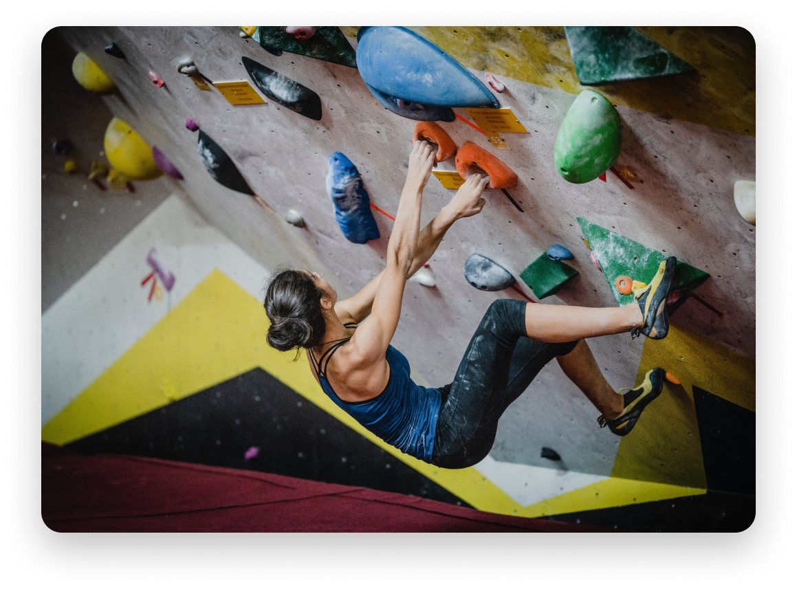 Woman rock-climbing in indoor rock-climbing gym