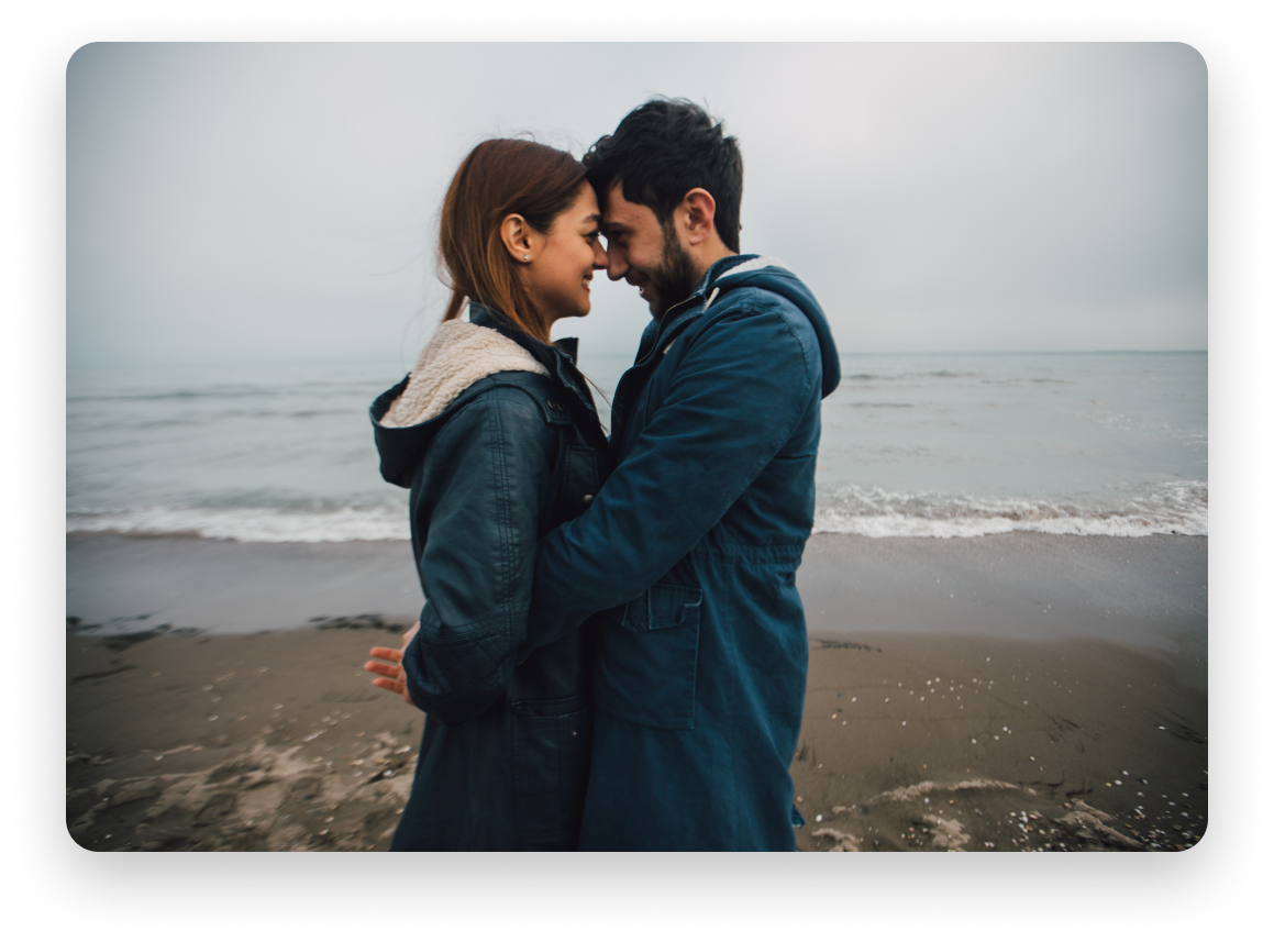 Couple facing each other in front of ocean