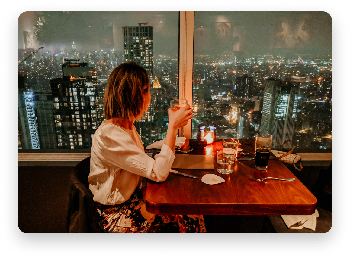 Woman holding a drink looking out at the city at night