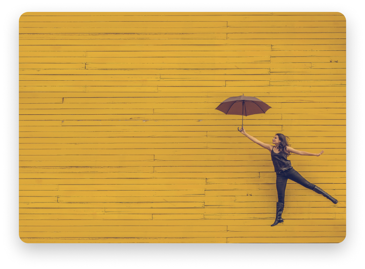 Woman jumping up with umbrella in front of yellow wall