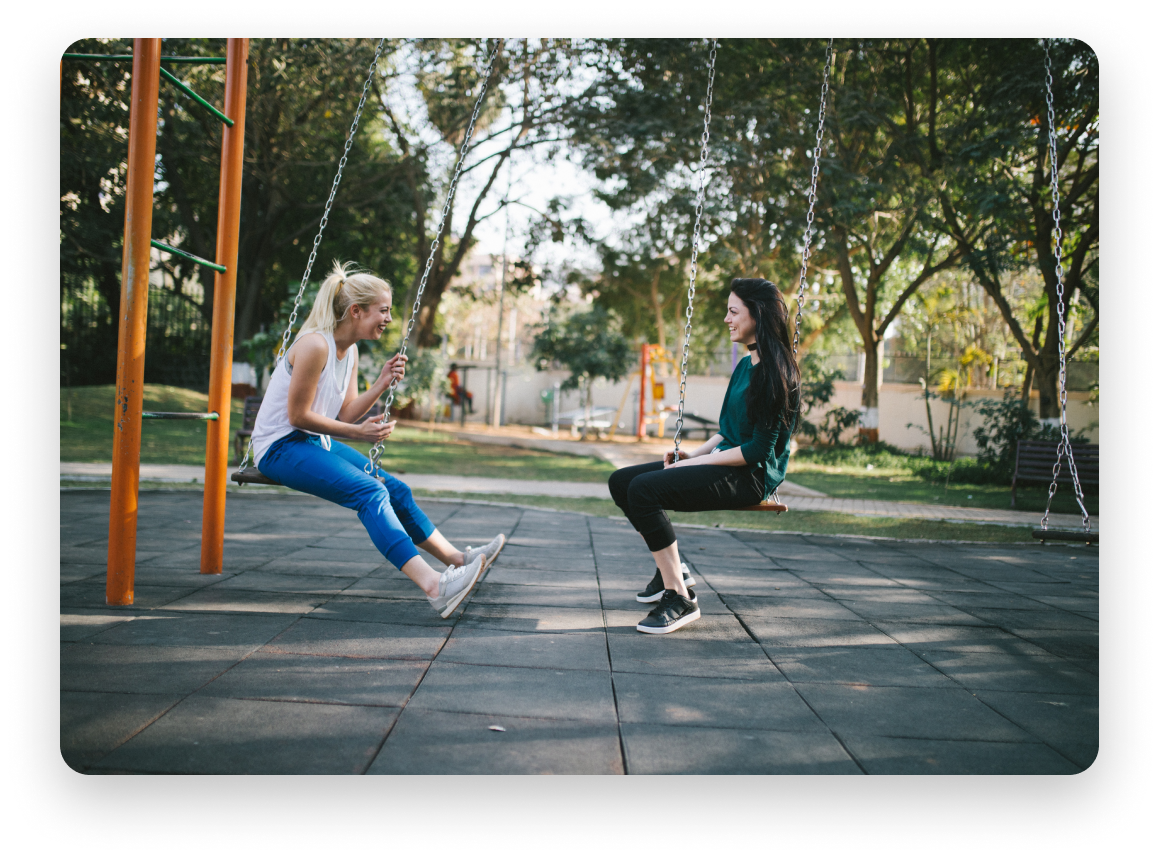 Two women facing each other on swings