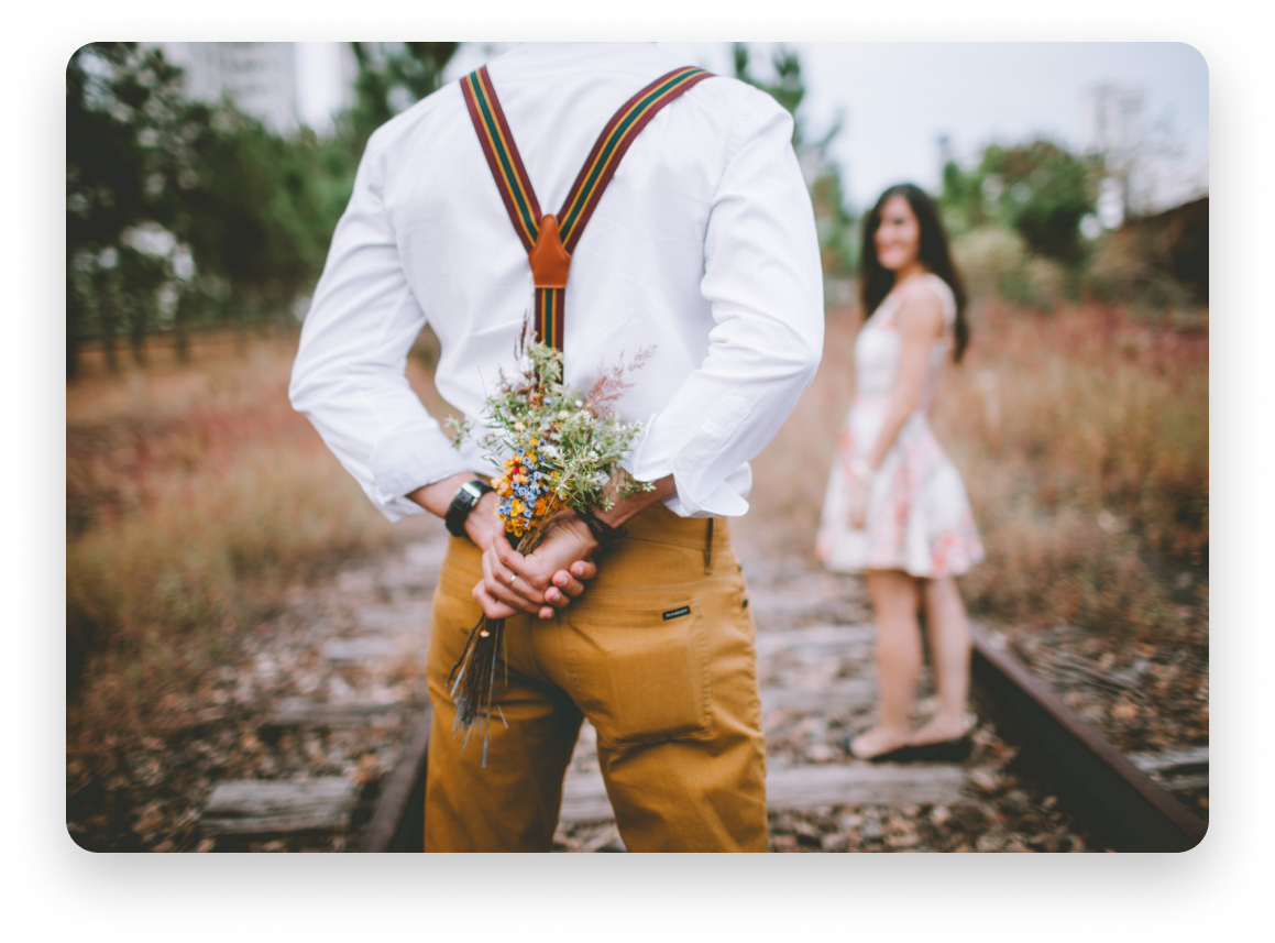 Man about to give woman flowers while standing in a field.