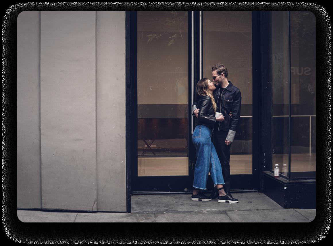 Homme et femme devant le bâtiment avec de grandes fenêtres, se serrant dans ses bras et riant.