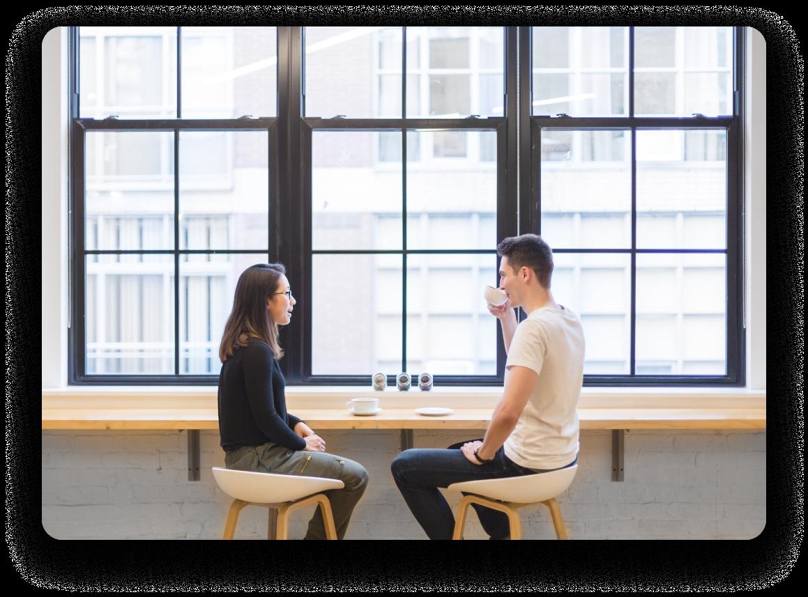 Homme et femme prenant un café ensemble à une longue table devant de grandes fenêtres.