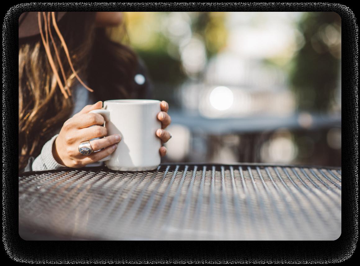 femme prenant un café assis à une table par une journée ensoleillée.