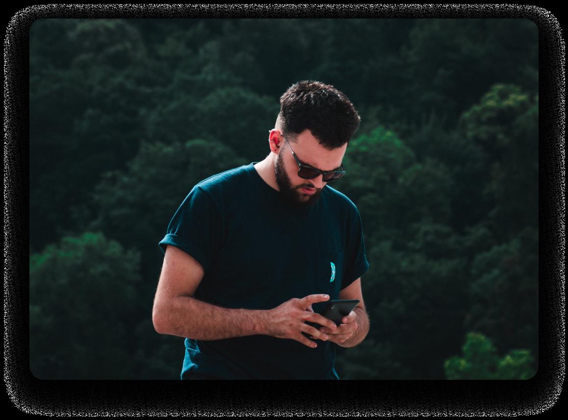 Homme avec des lunettes de soleil en t-shirt, arbres en arrière-plan, envoyant des SMS sur son téléphone.