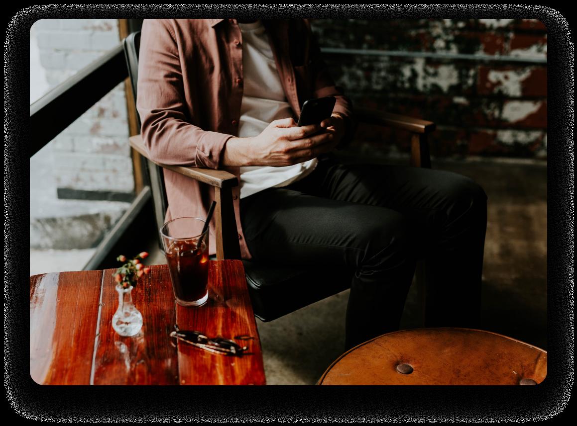 homme sur téléphone portable dans un café, en attente de date.