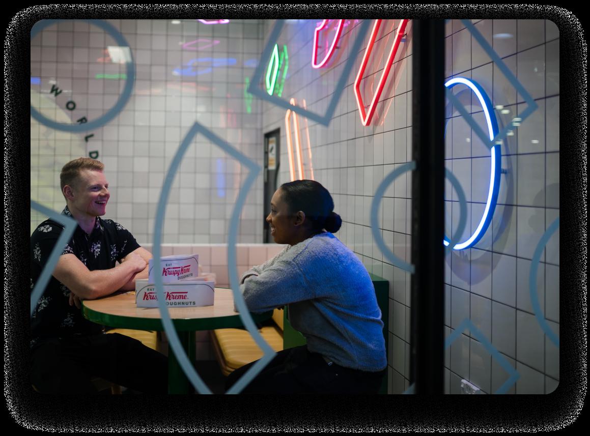 Homme et femme à une date dans un restaurant à la recherche rétro avec des beignets à la crème Krispy sur la table