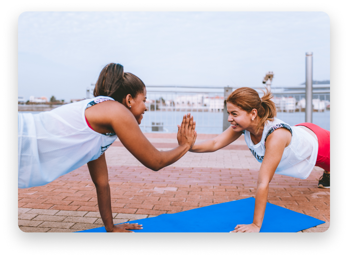 Two similing women doing push ups on a boardwalk in a clear day.