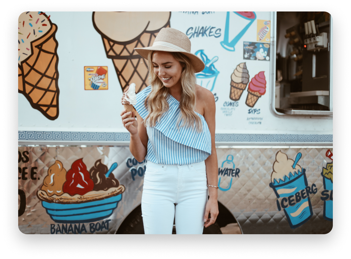 Woman wearing floppy hat and striped white and blue tope with white jeans holding an icecream cone in front of an icecream truck