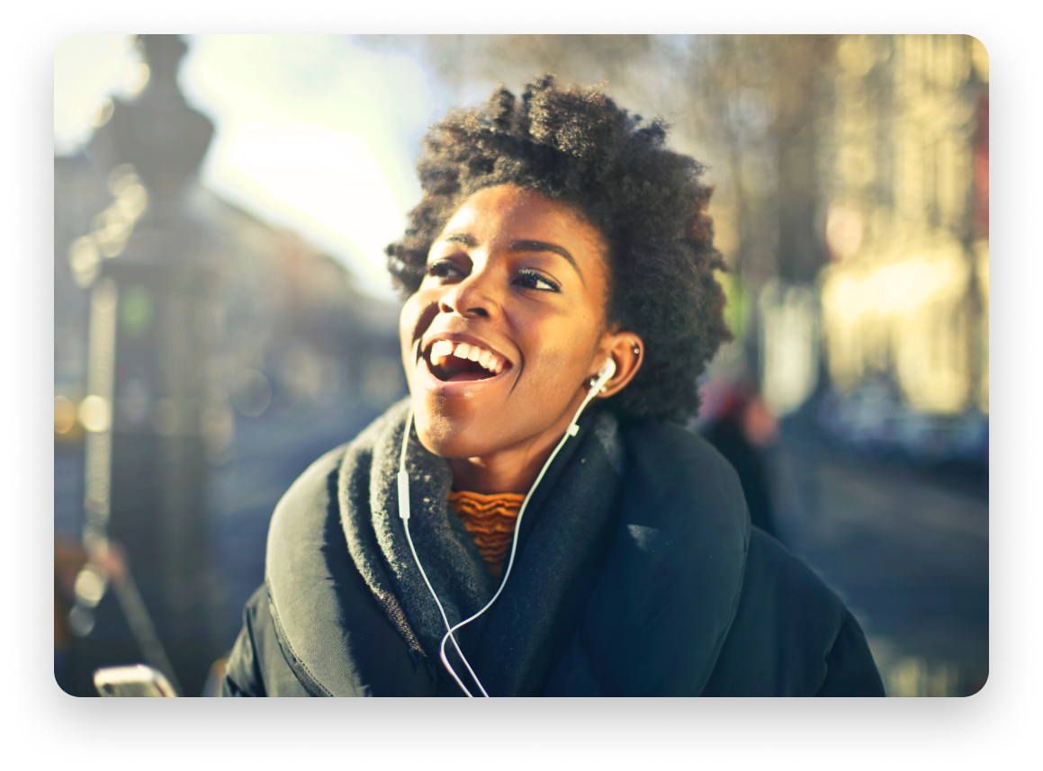 Woman listening to music with headphones, smiling on a beautiful sunny day