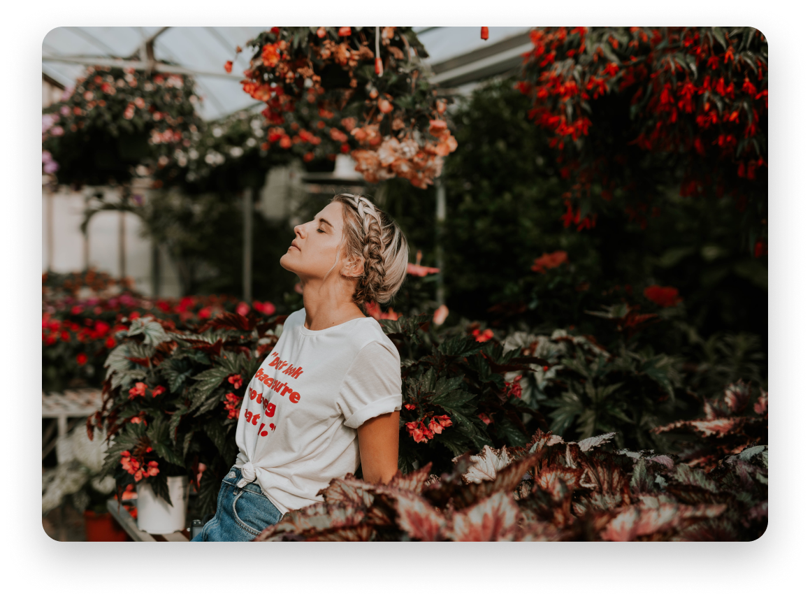 Blonde woman breathing in the air while standing amidst red, coral and orange hanging flower plants