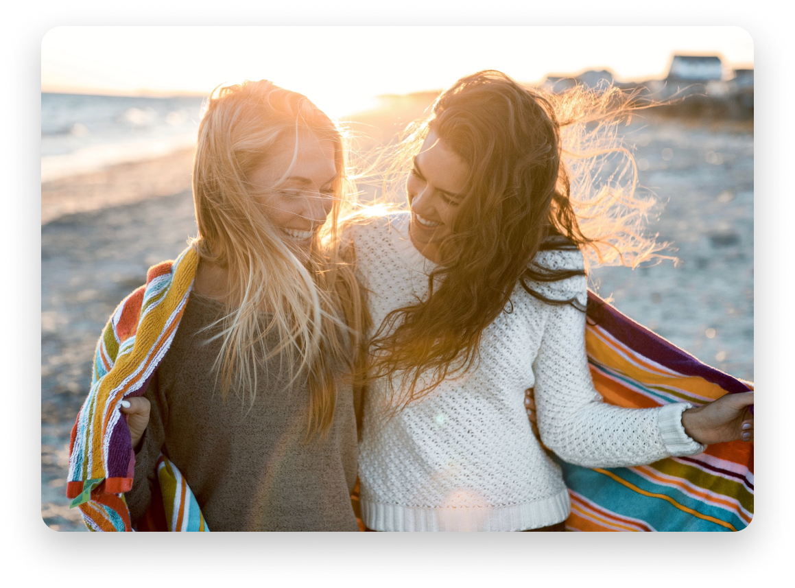 Two women, one blonde and one brunette on a beach together, laughing enveloped in a colourful blanket.