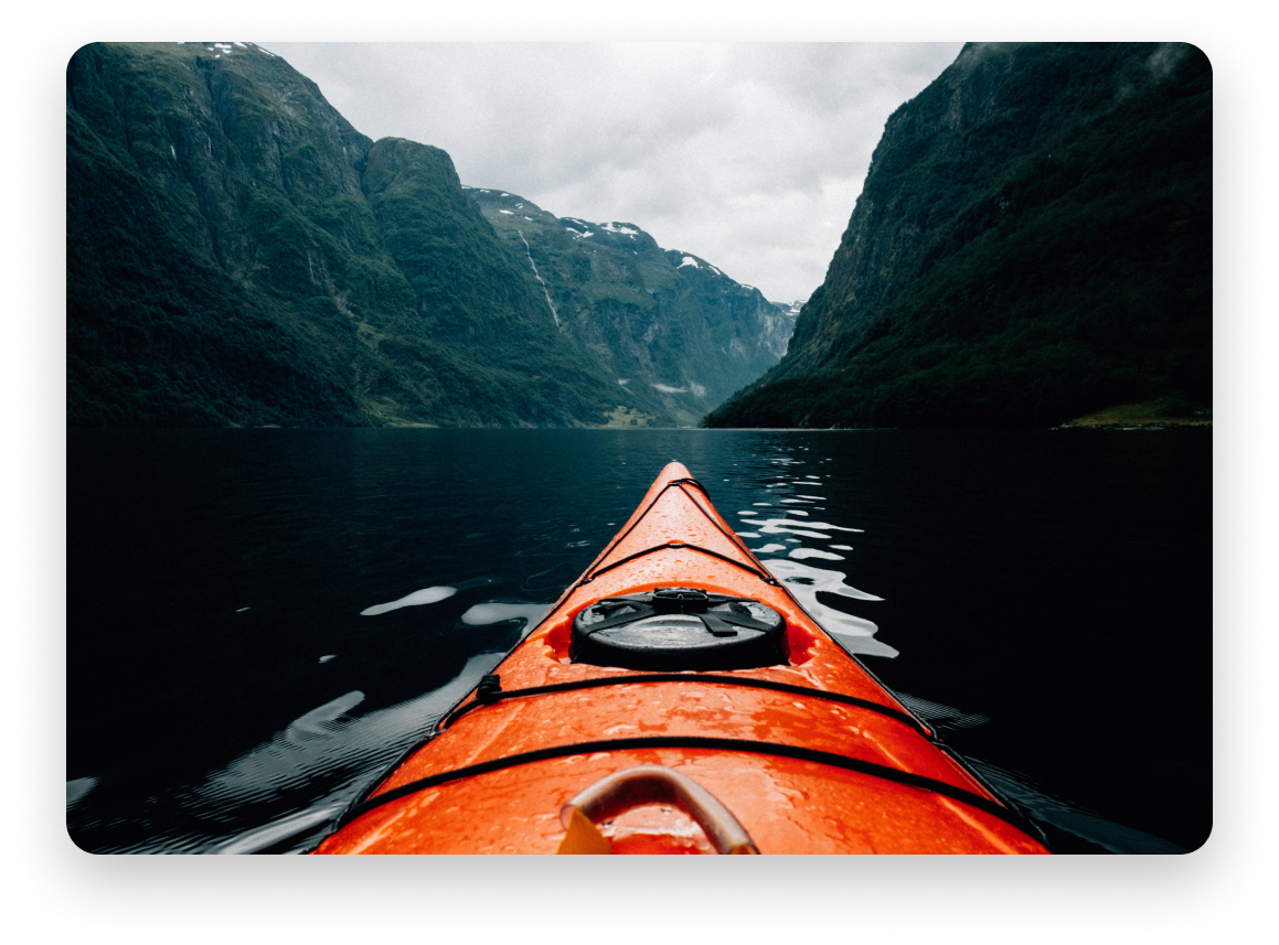 The tip of an orange kayak in a dark body of water between large mountains on either side.
