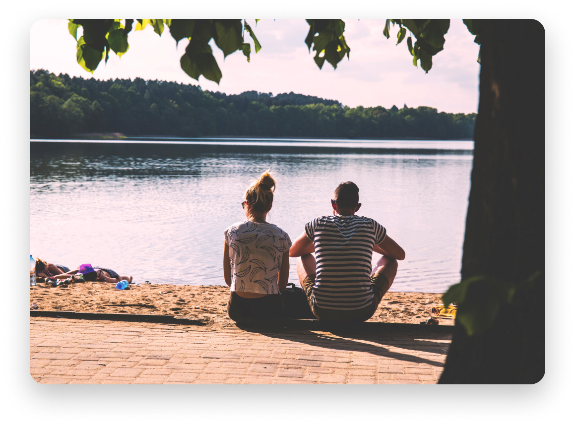 The backs of a man and woman staring at a lake with lush trees in the distance.