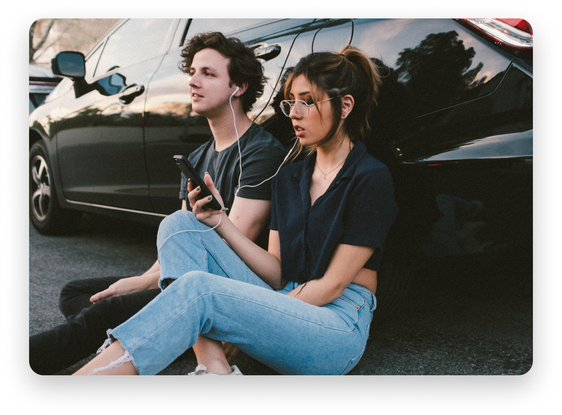 Man and woman leaning up against black car sharing headphones and listening to something on a cellphone